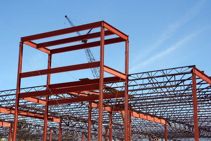 Ongoing framing and construction of a commercial shopping center.  A crane can be seen in the background working to lift and maneuver large pieces of steel into place.